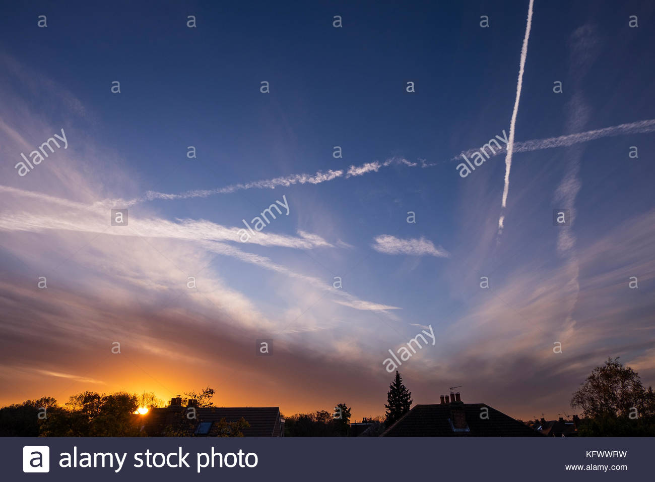 Wimbledon, London, UK. 1 November, 2017. Vapour trails and orange sunset clouds above rooftops in SW London. Credit: - Stock Image