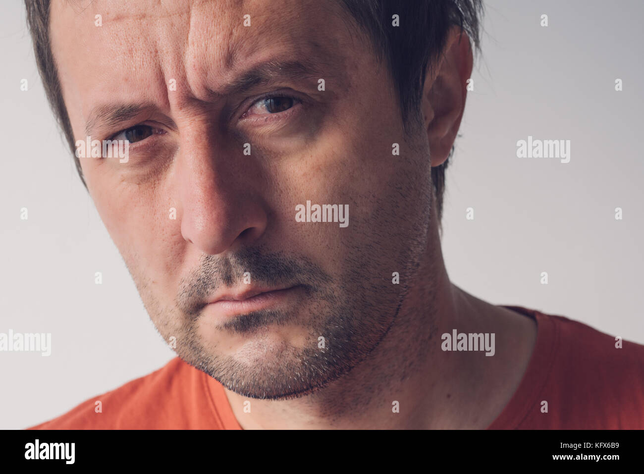 Serious portrait of adult caucasian man looking at camera, real people facial expressions - Stock Image