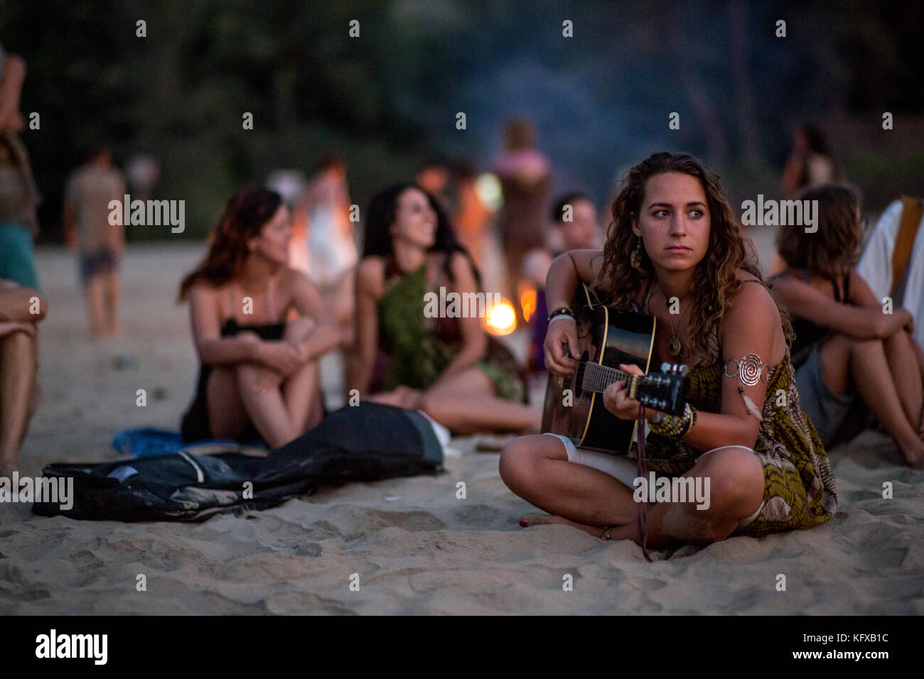Girl sitting in the sunset on a crowded beach with a guitar. - Stock Image