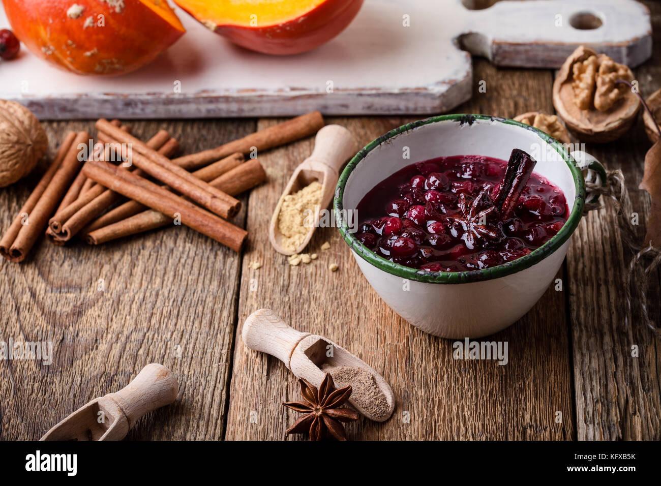 Homemade cranberry sauce in rustic mug, preparation Thanksgiving dinner - Stock Image