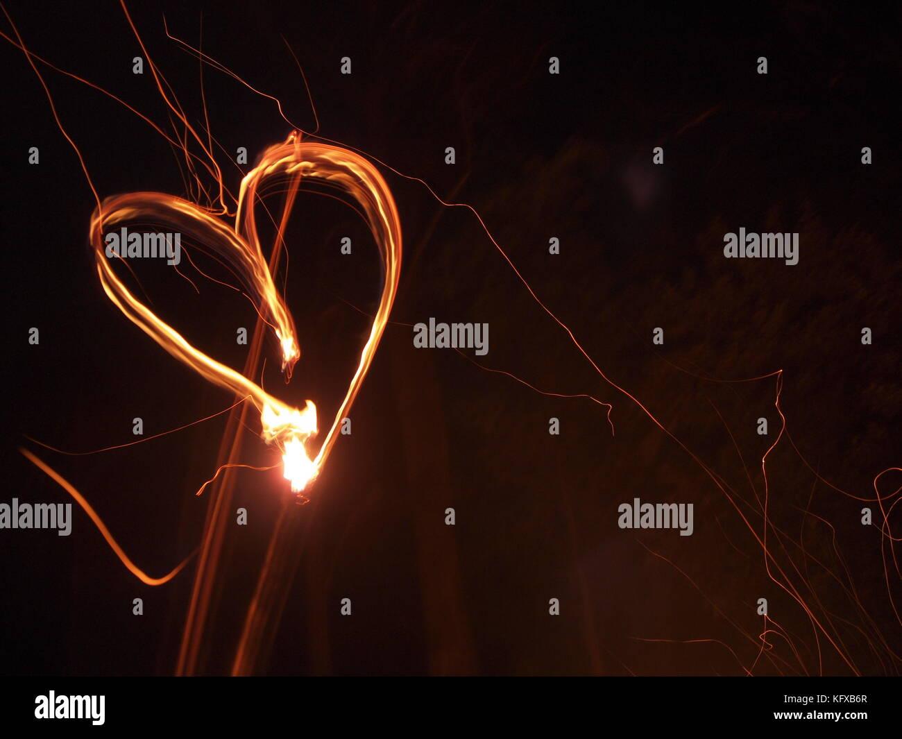 Glowing Heart in the dark Stock Photo