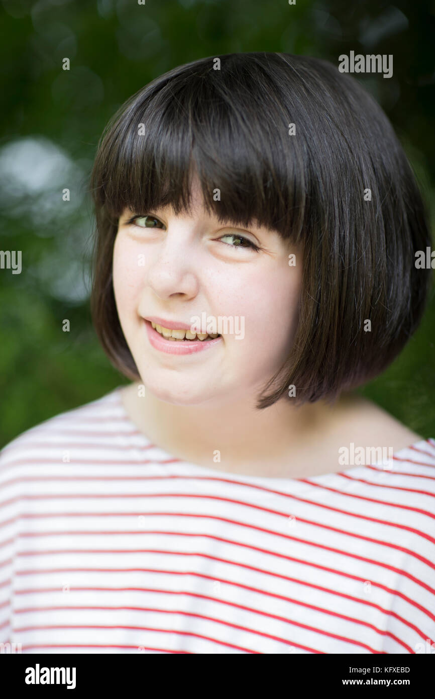 Outdoor Head And Shoulder Portrait Of Smiling Pre Teen Girl - Stock Image