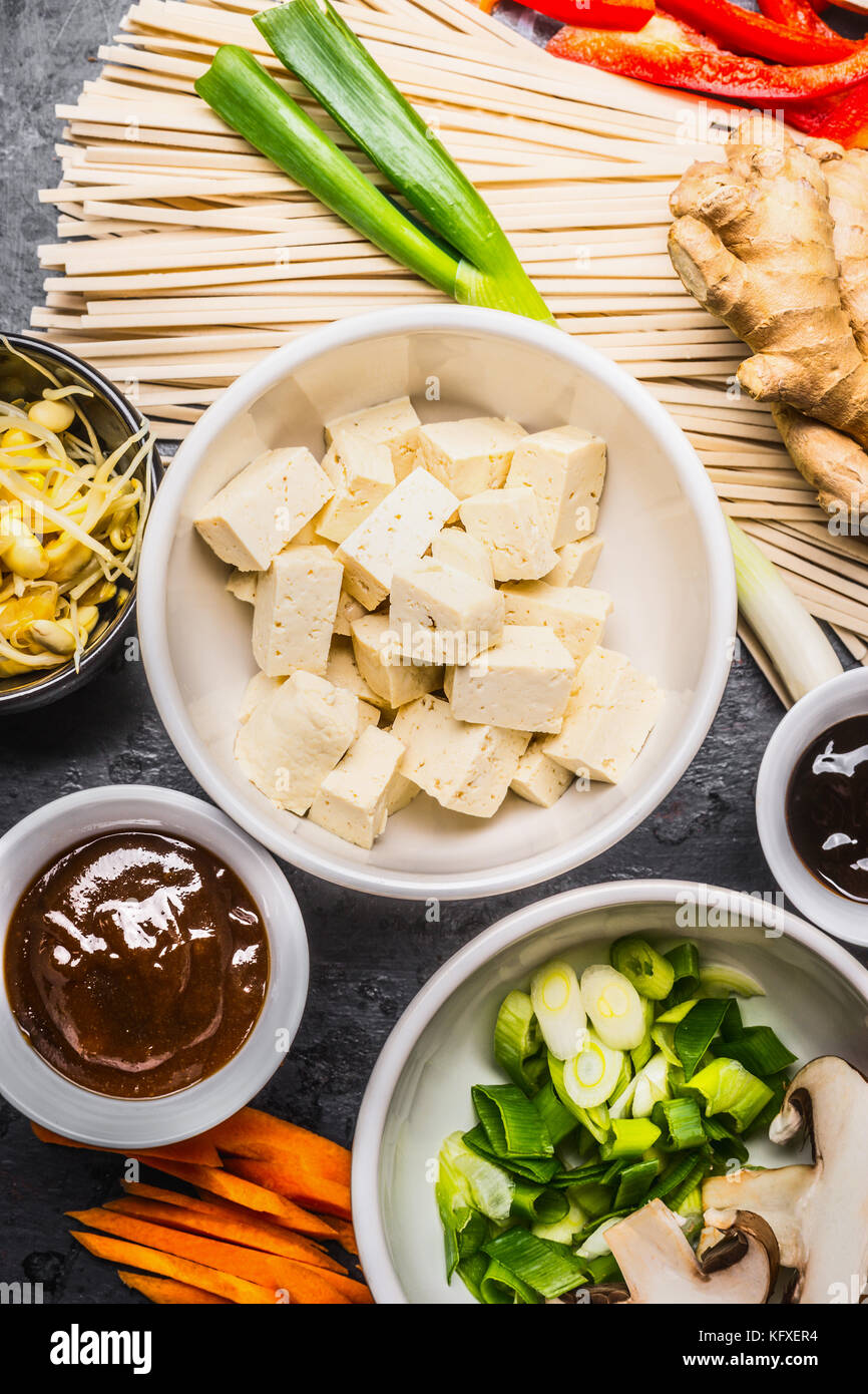 Asian food ingredients: tofu, noodles, ginger, cut vegetables, Sprout,green onion and hoisin sauce for tasty cooking, - Stock Image