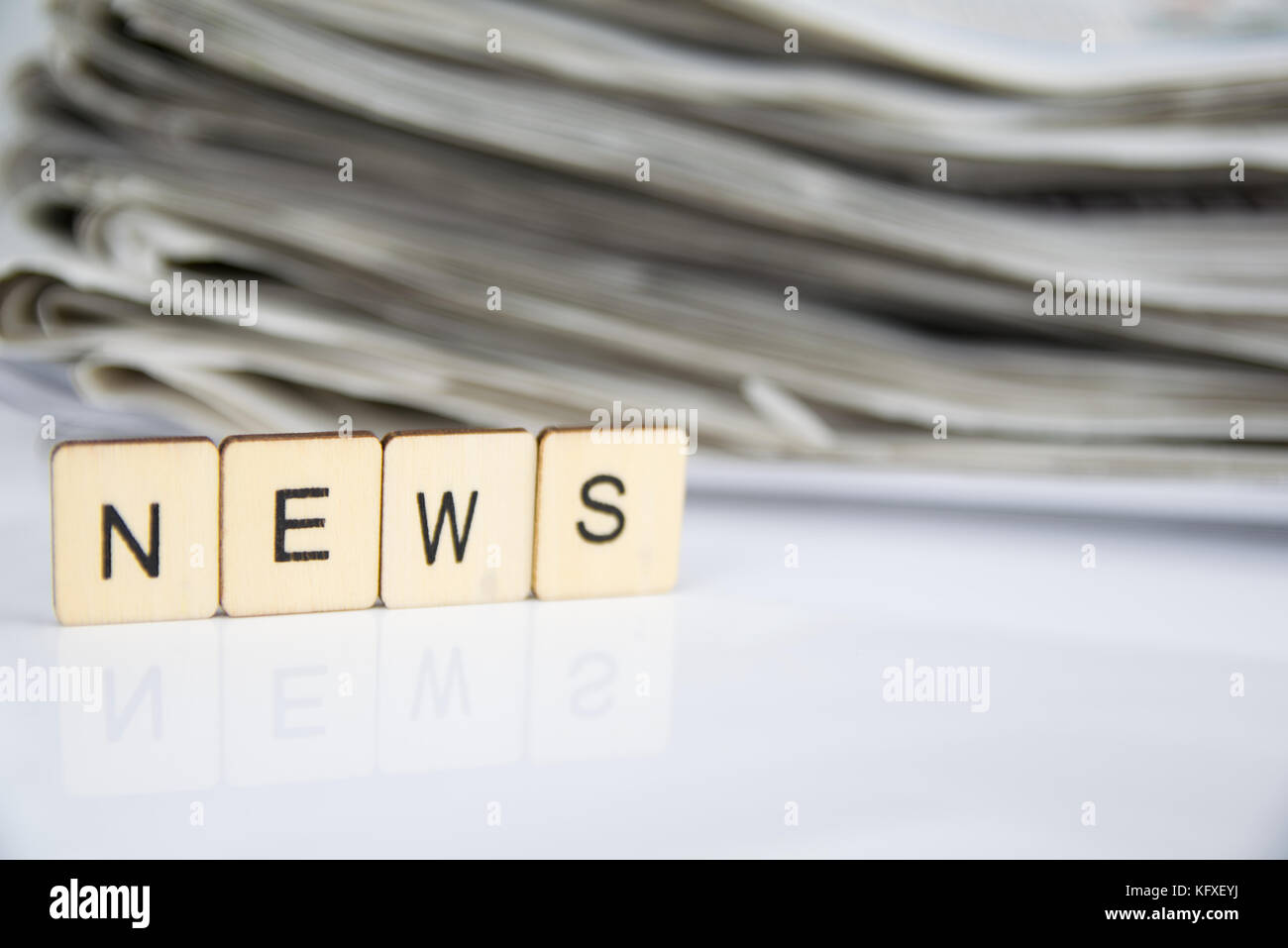 the word news written in letter tiles on a reflective white surface