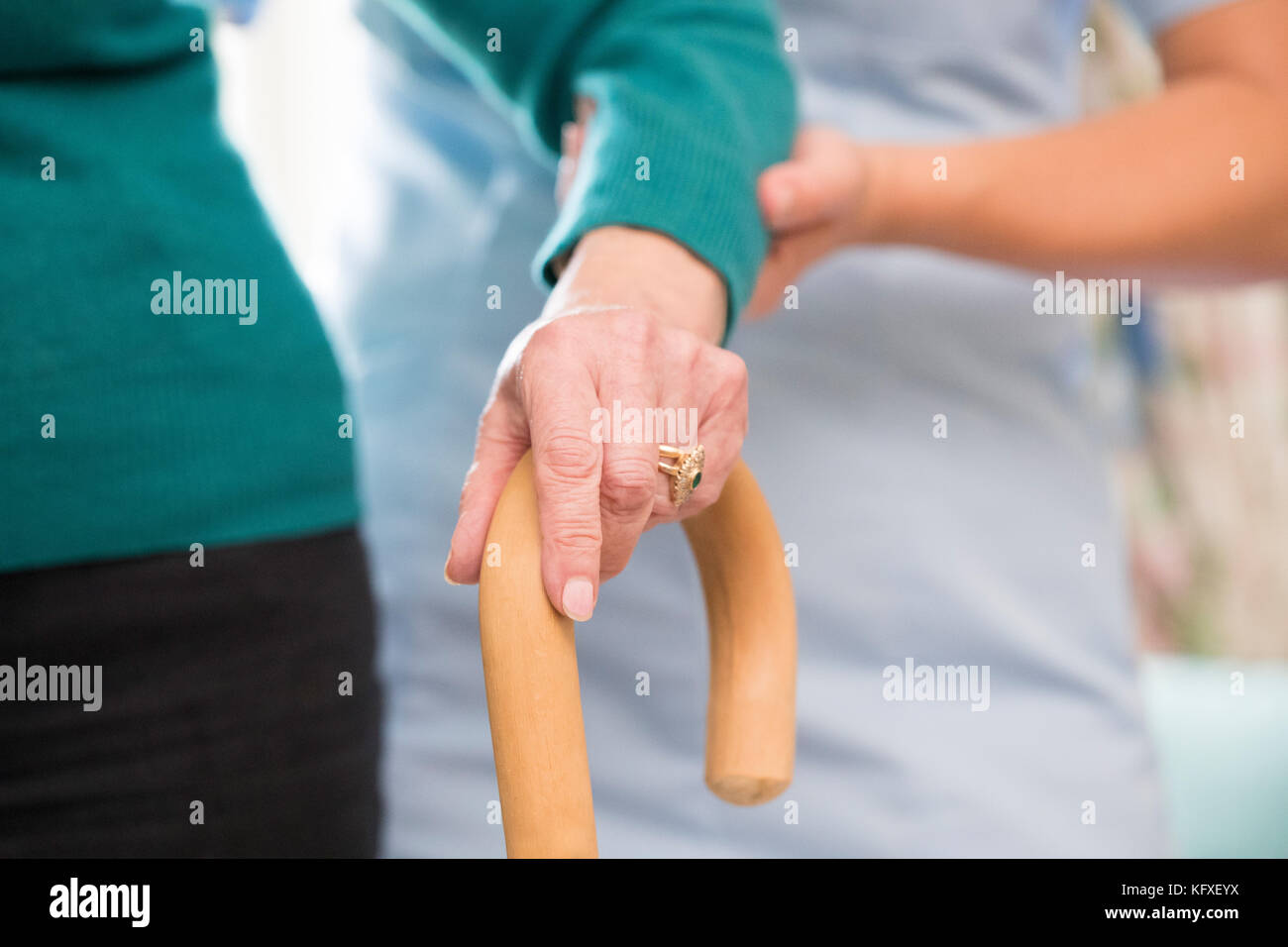 Senior Woman's Hands On Walking Stick With Care Worker In Background - Stock Image
