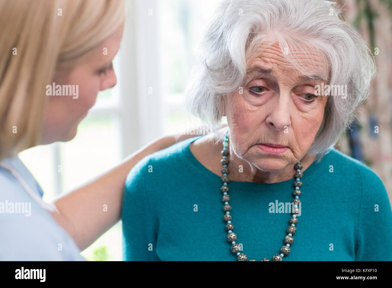 Care Worker Talking To Depressed Senior Woman At Home Stock Photo