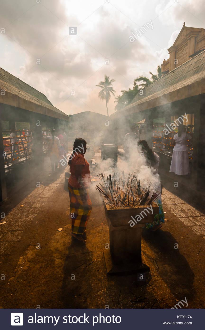 Buddhist Pilgrims lighting incense sticks outside the Sri Maha Bodhi. The sacred bodhi tree. Anuradhapura, North Stock Photo