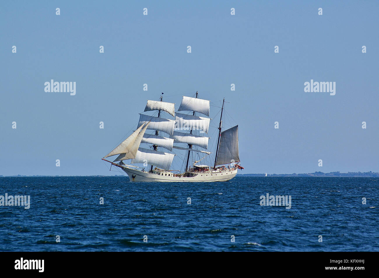 Square-rigged white sailing ship at sea with a distant shore in the far background - Stock Image