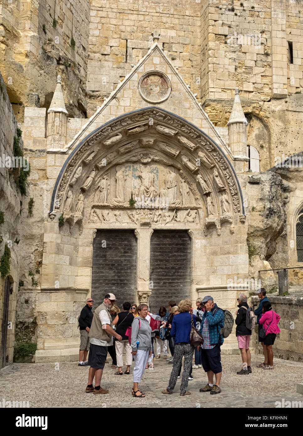 SAINT-ÉMILION, FRANCE:A group of sightseers outside the the Monolithic Church - Stock Image