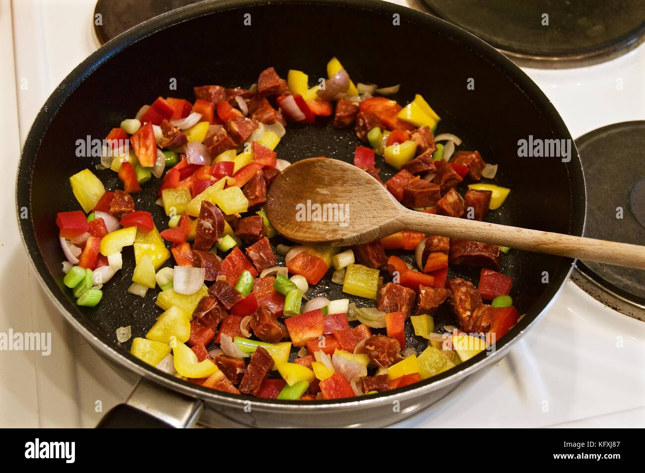 Cooking a seafood paella on the hob in a teflon coated wok with wooden spoon - Stock Image