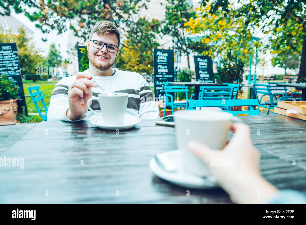 couple sitting in cafe outaside - Stock Image