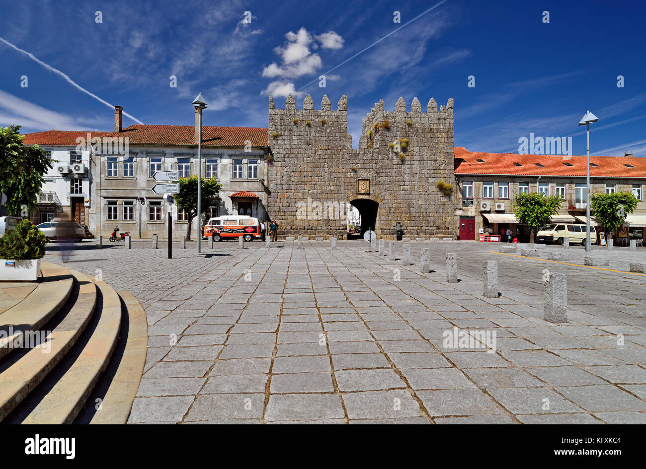 Wide stone paved square with medieval entrance gate leading to historic center in Trancoso - Stock Image