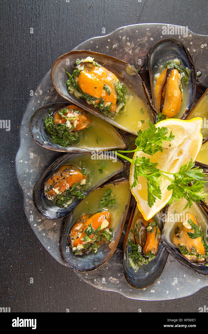 Mussels baked with butter and parsley in shell mussels. Lemon, parsley and spices around plate on dark background. - Stock Image