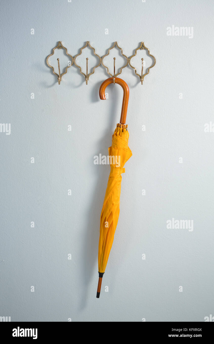 Yellow umbrella hanging on hook against white wall - Stock Image