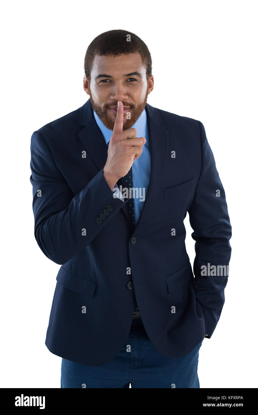 Businessman standing with finger on lips against white background - Stock Image