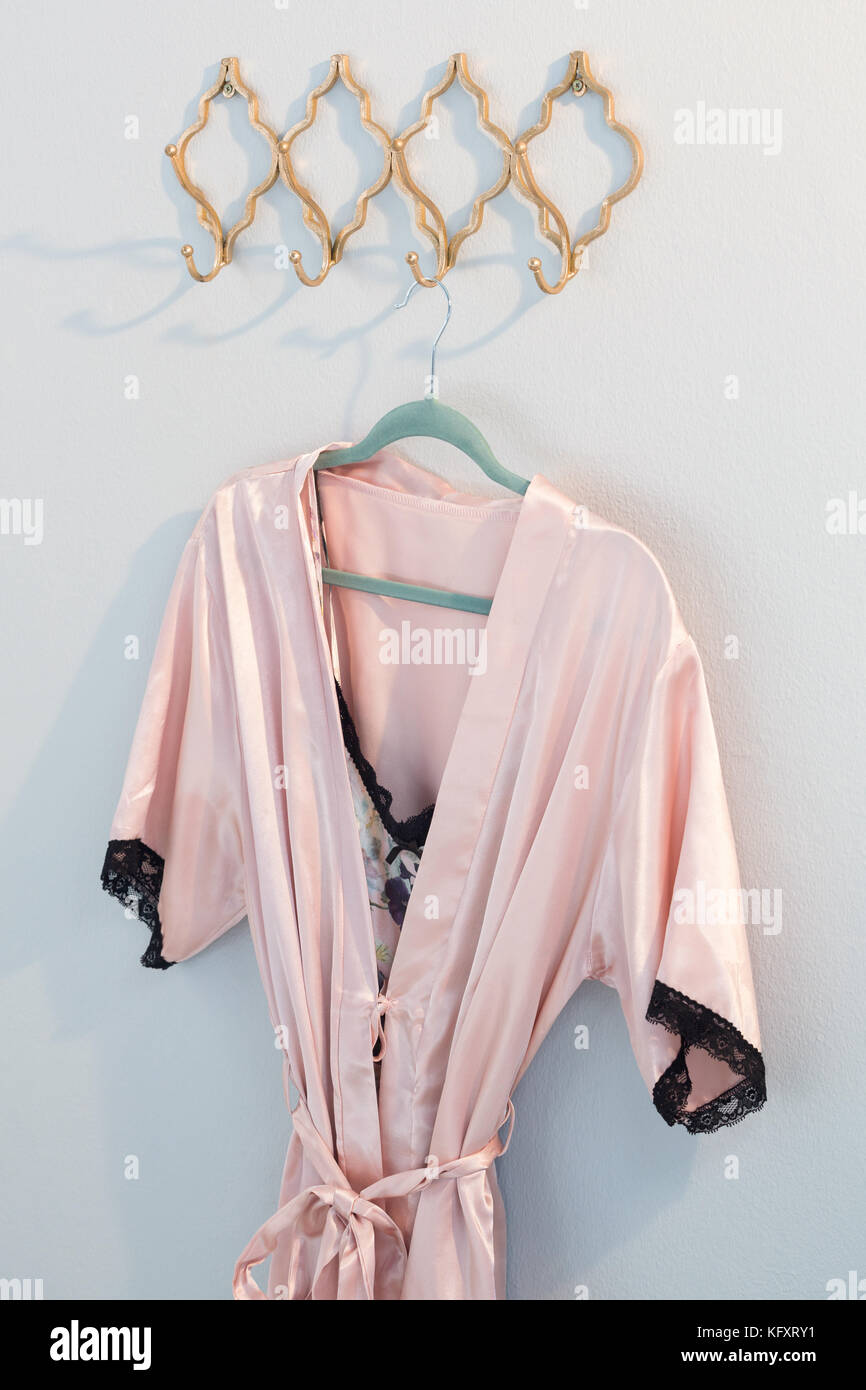 Nightwear hanging on hook against white wall - Stock Image