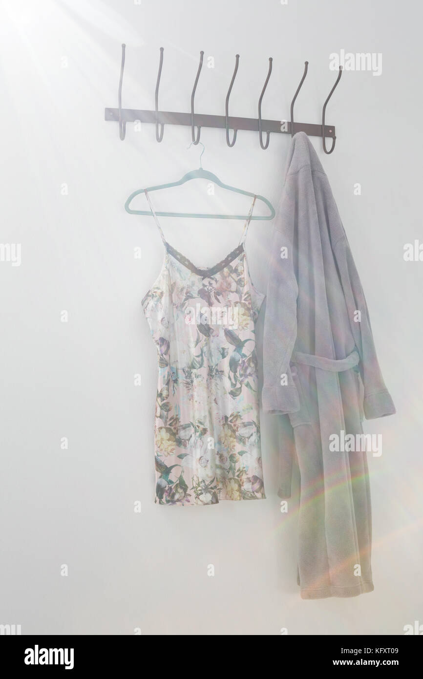 Bathrobe and nightwear hanging on hook against white wall - Stock Image