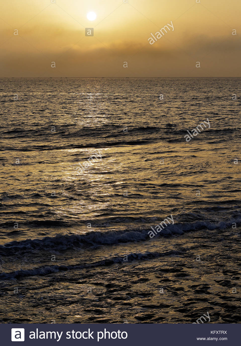 Fishing fleet on the horizon, Sun with sea mist, early morning, River Tagus, Lisbon, Portugal - Stock Image