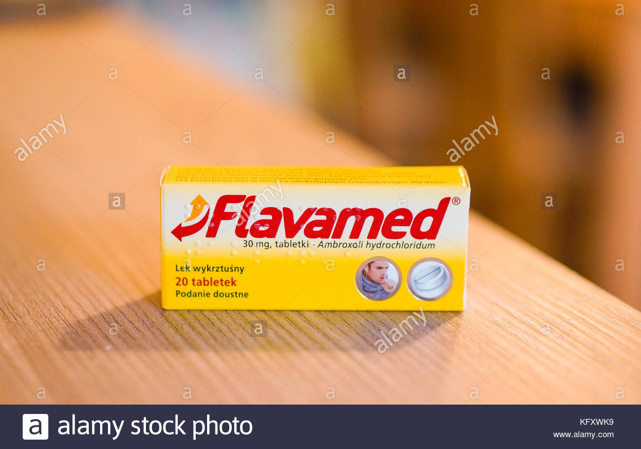 Flavamed coughing pills in a box on a wooden table - Stock Image