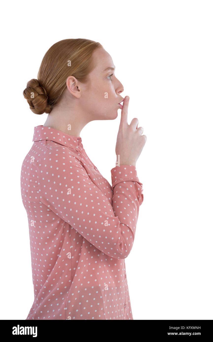 Beautiful woman with finger on lips against white background - Stock Image