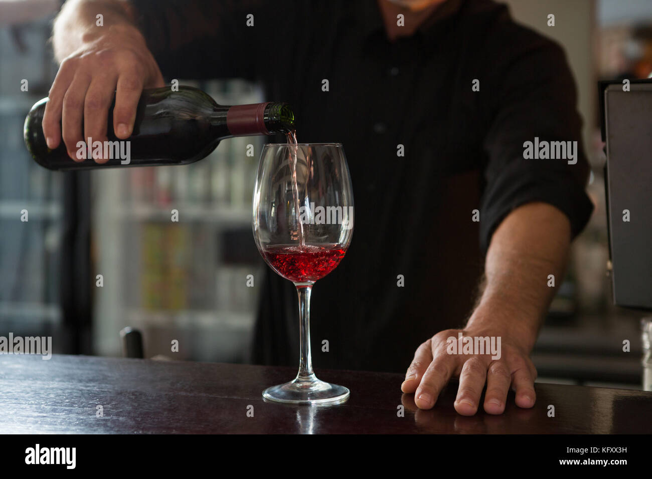 Mid-section of waiter pouring wine in the glass - Stock Image