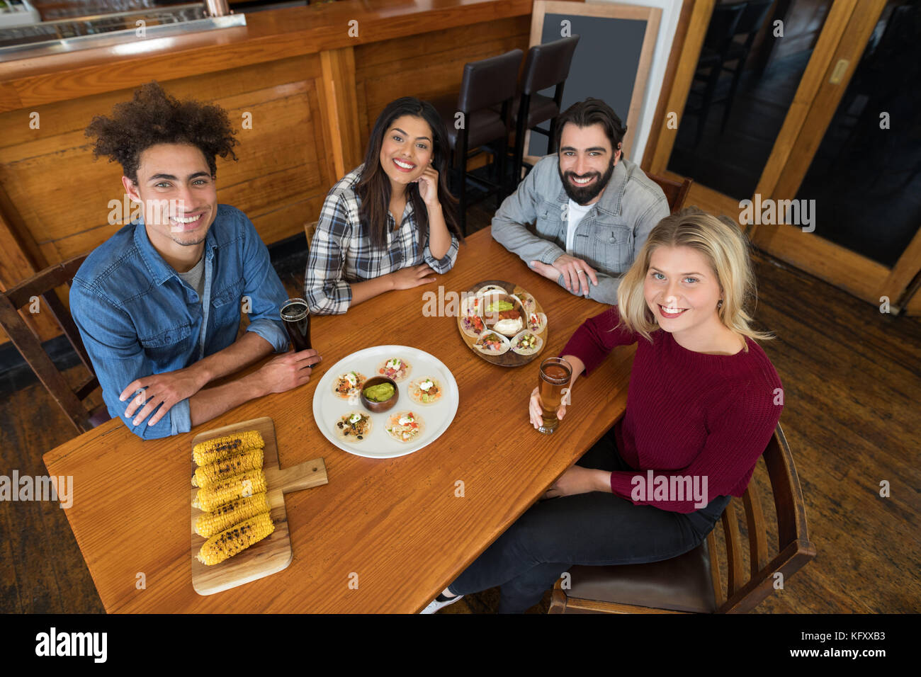 Happy friends sitting together with baby corn, snacks and beer on table in bar - Stock Image