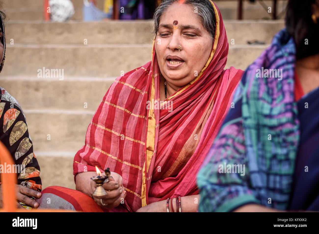 Hindu woman chanting and counting mantras for offering in
