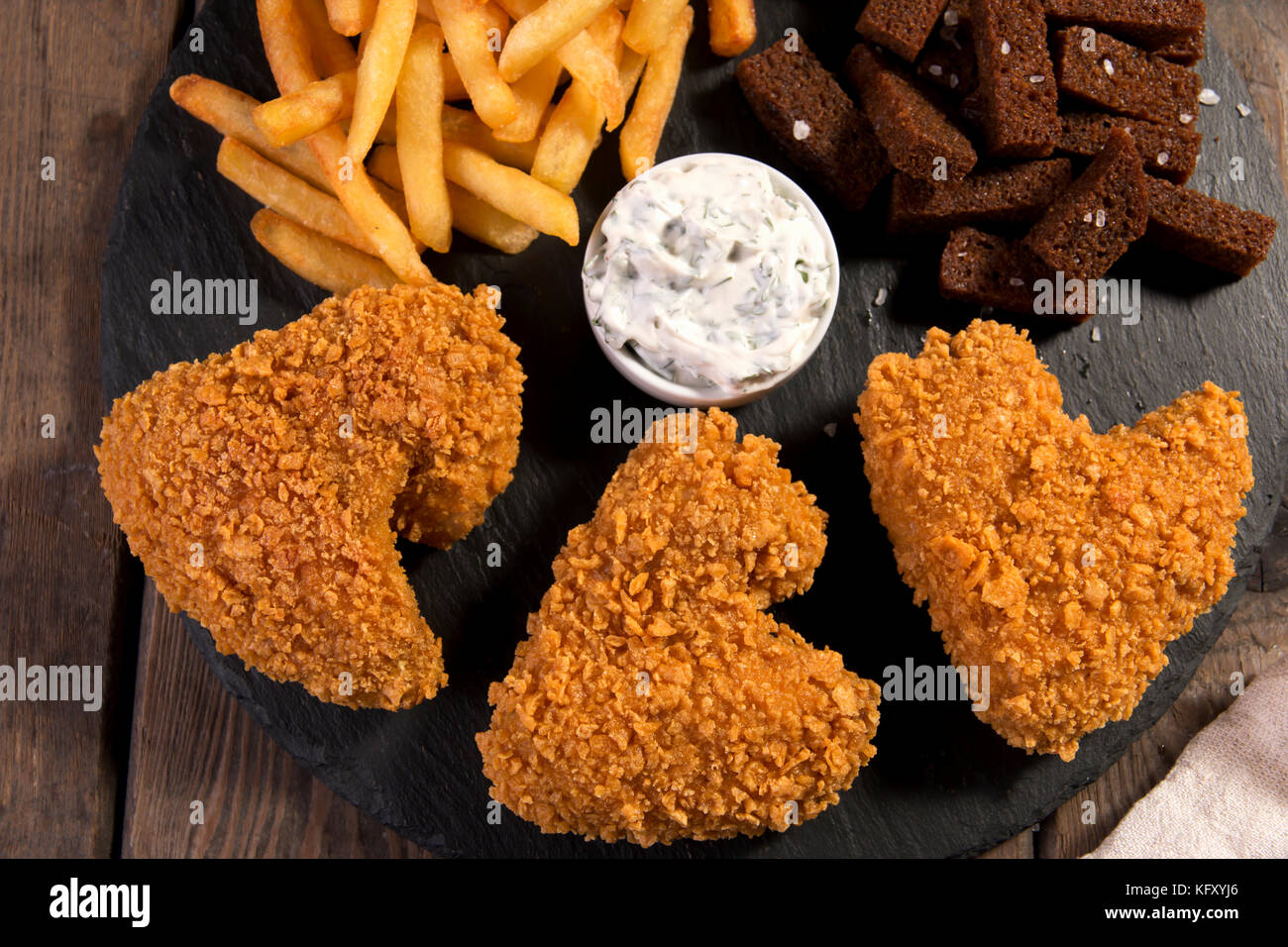 fried chicken wings breaded crispy with french fries fried rye bread croutons beer snack - Stock Image