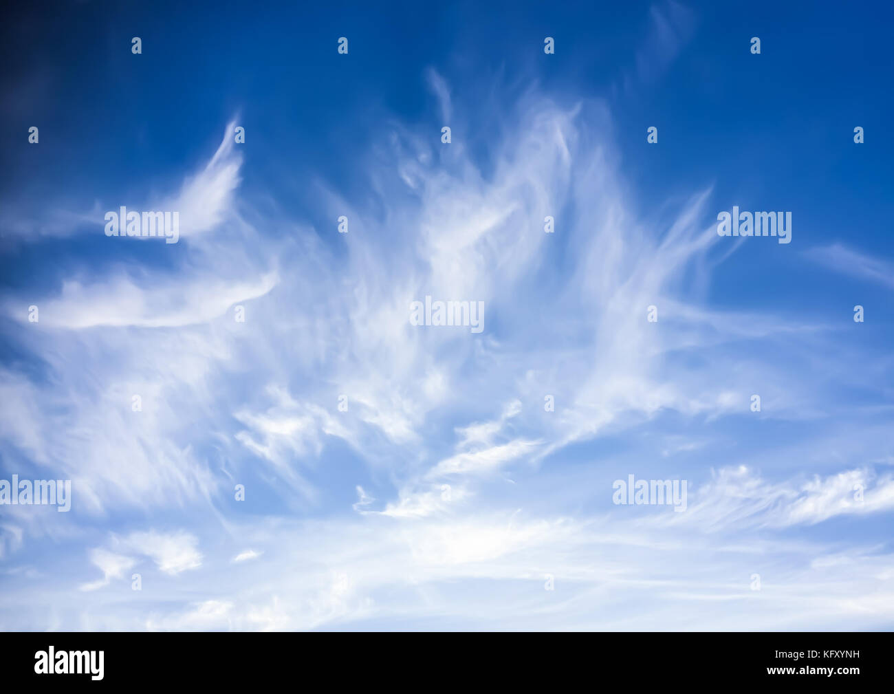 An abstract shot of a dramatic wispy cloud formation in a blue sky. - Stock Image