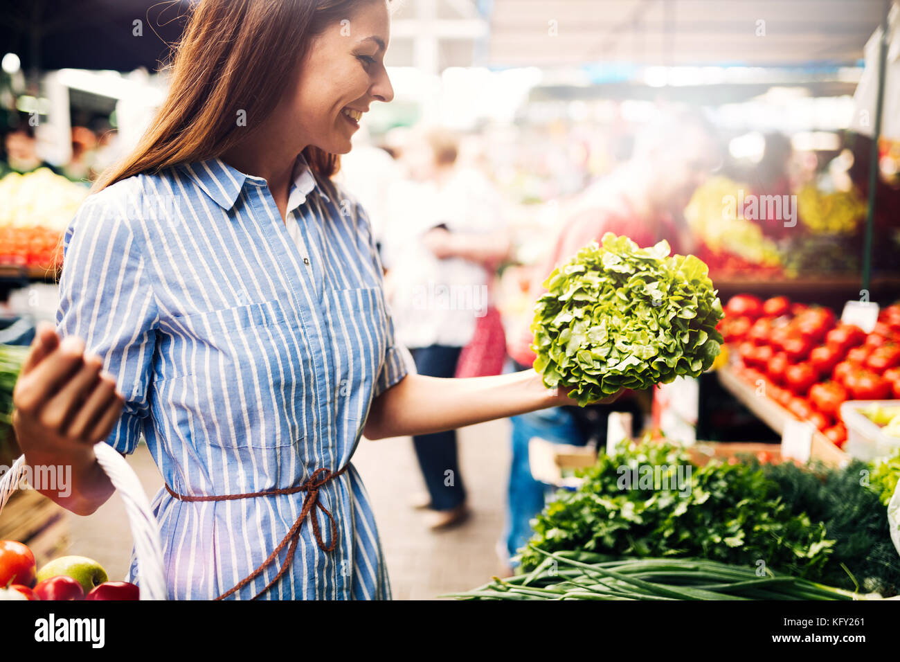 Picture of woman at marketplace buying vegetables - Stock Image