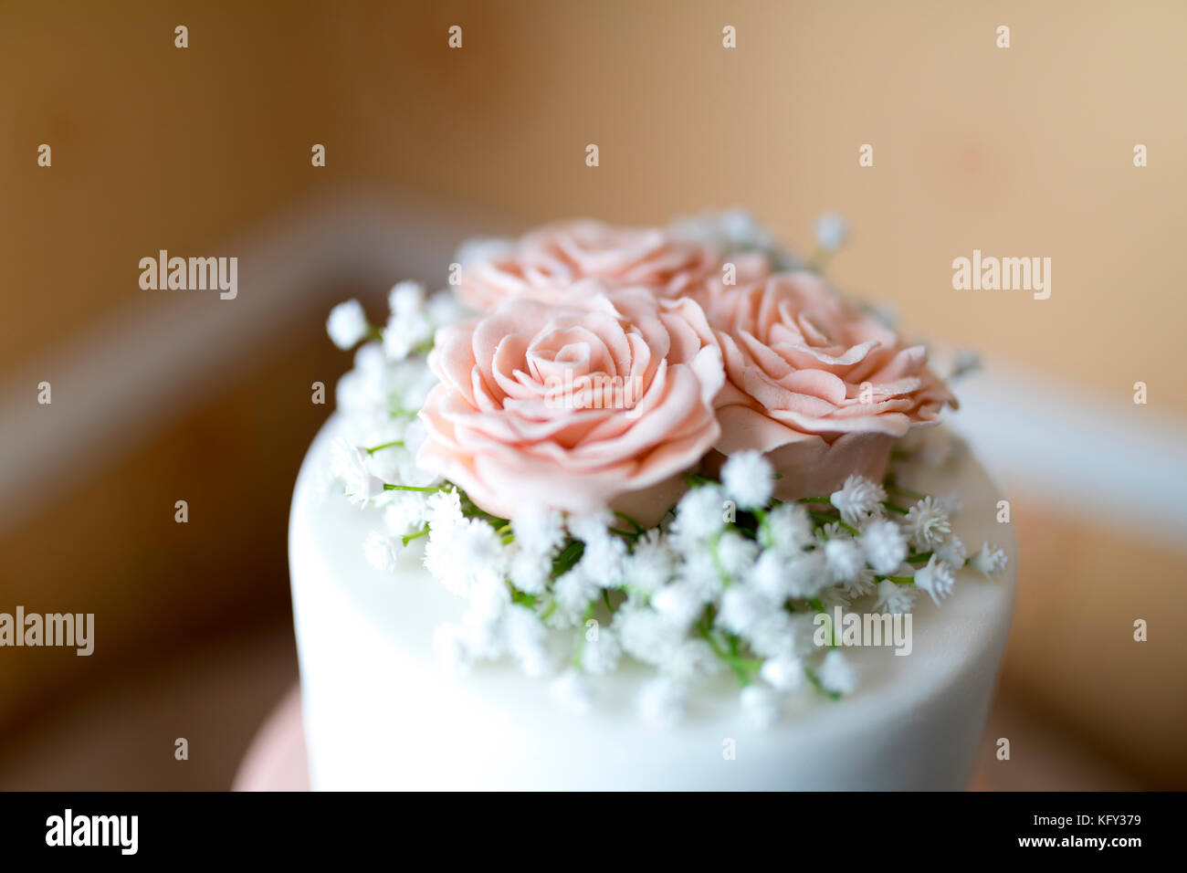 Close up of a pink icing fondant rose petals with babies breath decoration on top of a beautiful wedding cake in - Stock Image