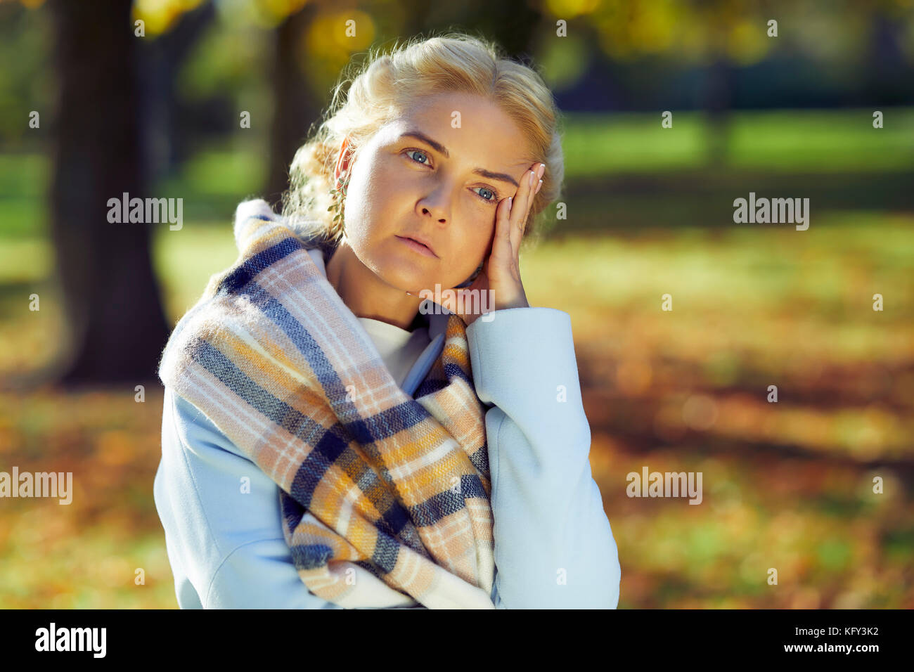 Woman looking concerned outdoors - Stock Image
