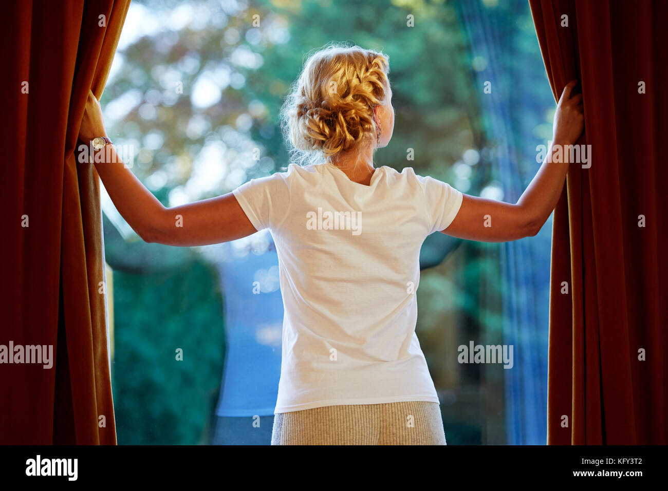 Woman opening curtains - Stock Image