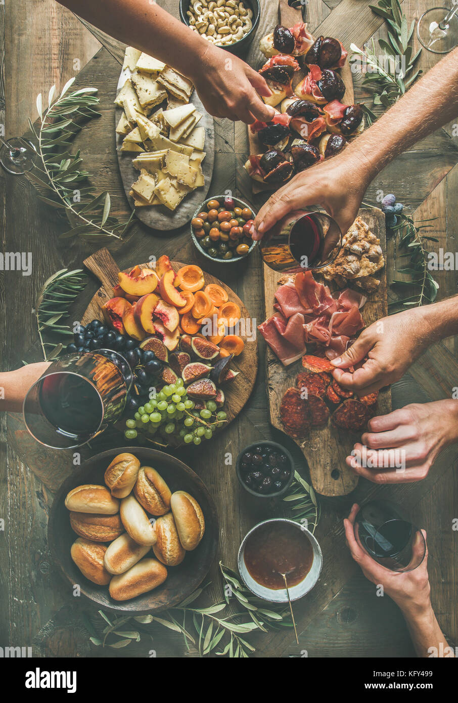 Flat-lay of friends hands eating and drinking together - Stock Image
