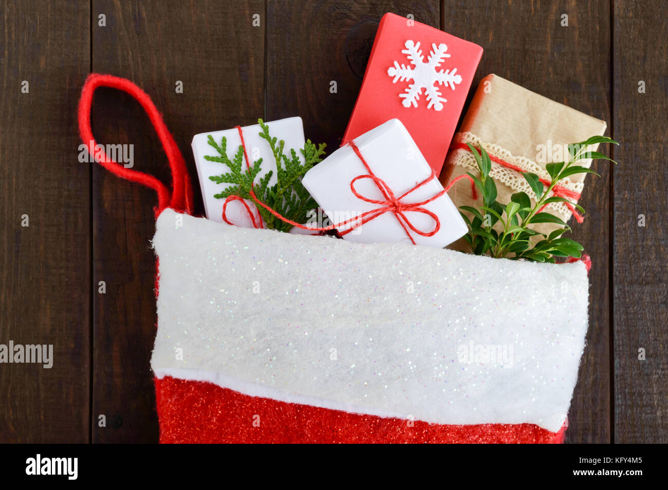 Christmas, New Year's boot for gifts, full of gift boxes on a dark wooden background. Theme of winter holidays. - Stock Image