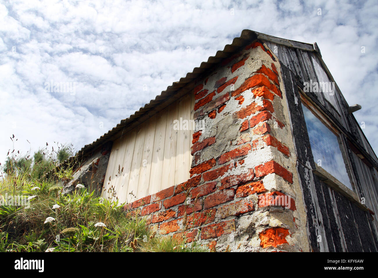 Red brick outbuilding or shed under cloudy sky - Stock Image