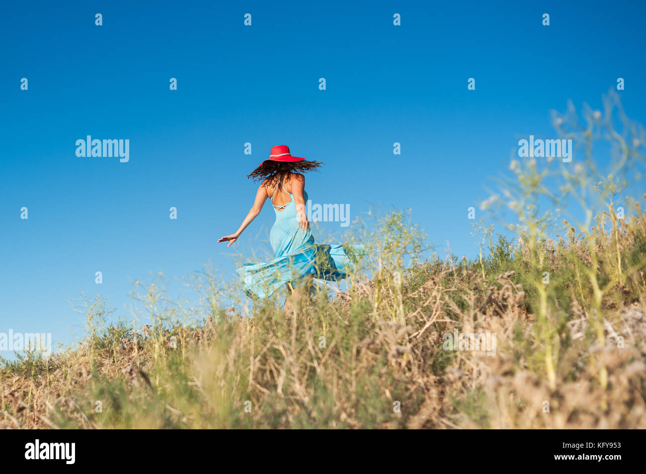 Beautiful woman in blue dress dancing and enjoying nature at the Antelope Valley California Poppy Reserve in Lancaster, - Stock Image