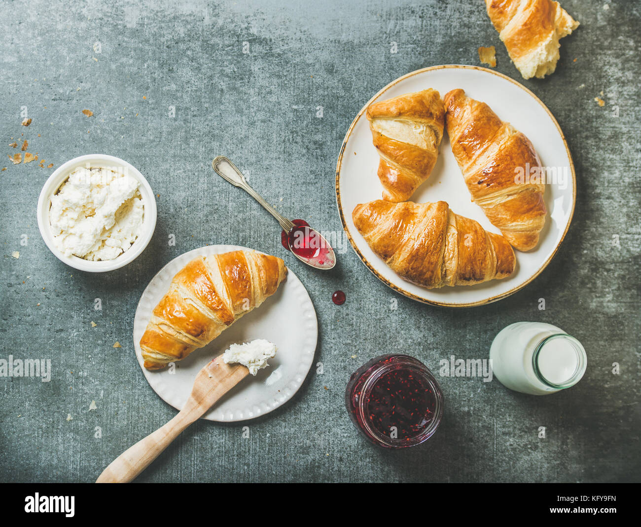 Freshly baked croissants with jam, cream-cheese and milk in bottle - Stock Image