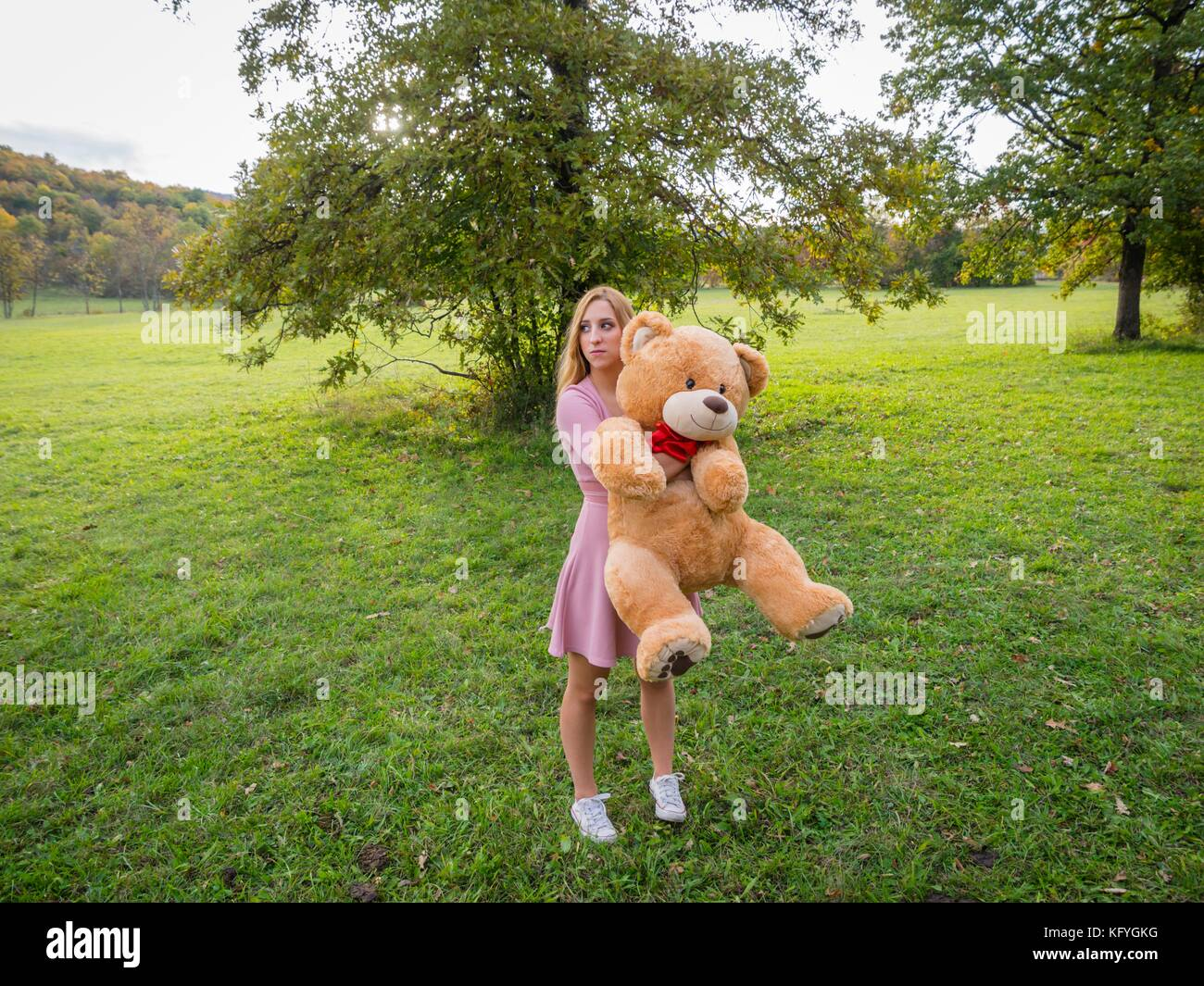 Cute teen girl and big teddy-bear toy lost in nature solitude - Stock Image