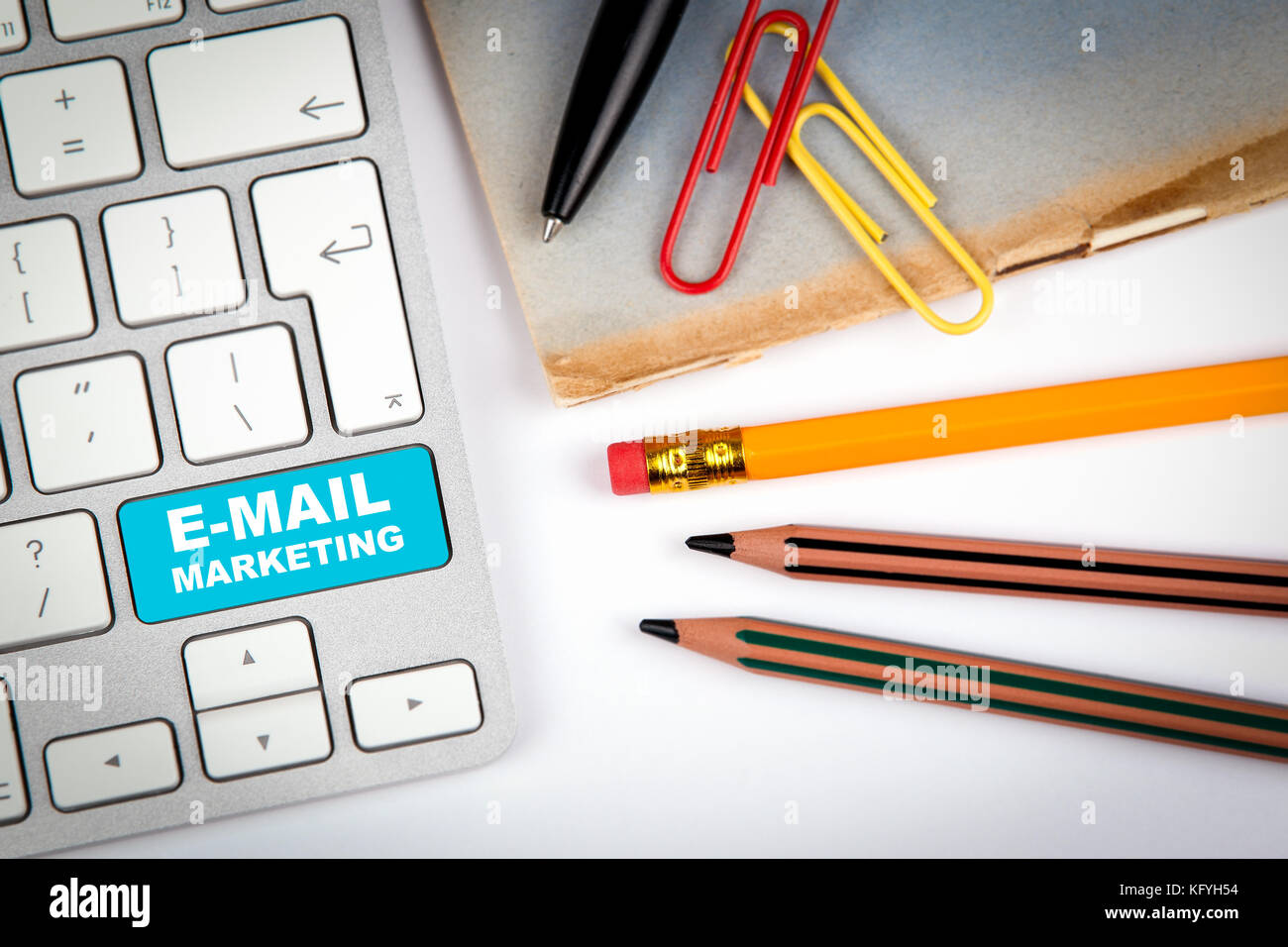 E-Mail Marketing concept. Computer keyboard on a white office desk with various items - Stock Image