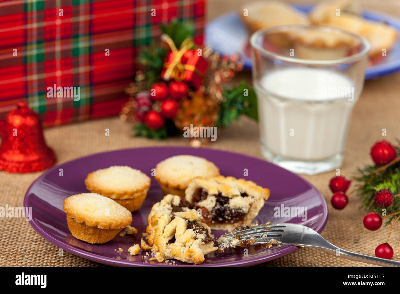 Broken mince pie on a purple plate with a glass of milk on a christmas table with a hessian tablecloth - Stock Image