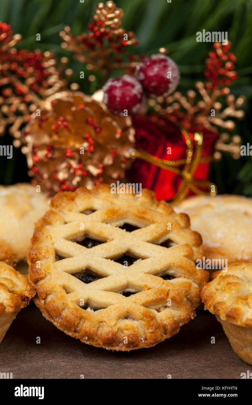 Close up of a lattice top mince pie with some christmas decorations in the background - Stock Image