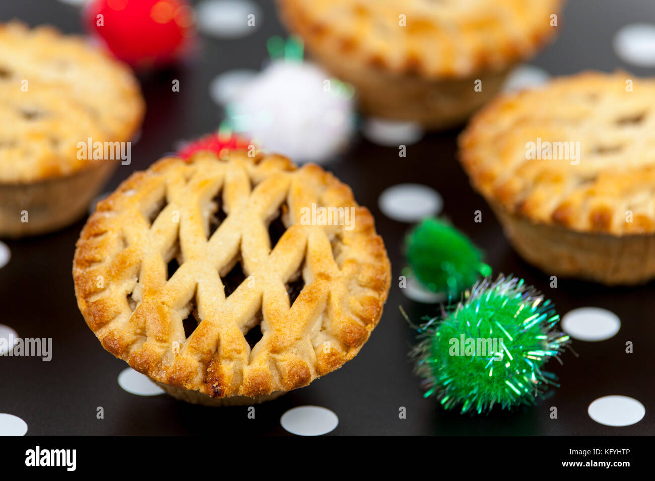 Fresh golden brown lattice top mince pies against a decorated christmas background - Stock Image