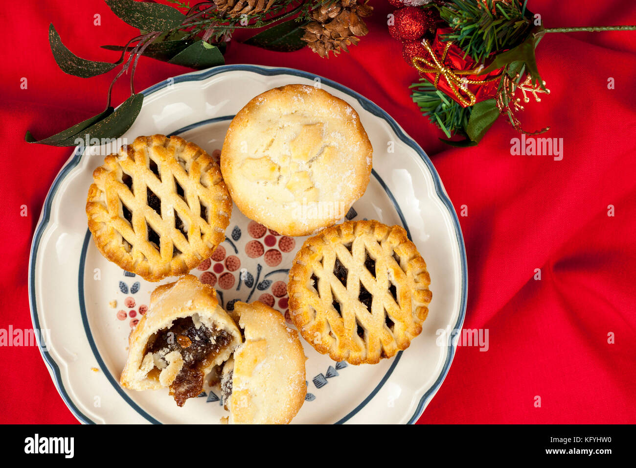 Plated lattice top mince pies at christmas on a ruffled red table cloth with some festive seasonal decorations - Stock Image