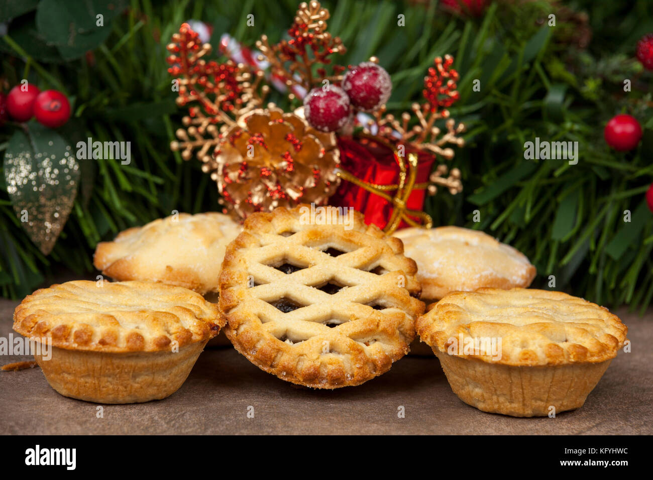 Selection of golden brown mince pies with festive christmas decorations in the background - Stock Image