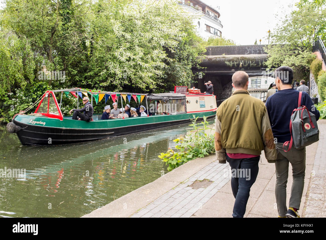 Narrowboat or barge passing on the Regents Canal with people walking in the canalside towpath near Camden Town, - Stock Image