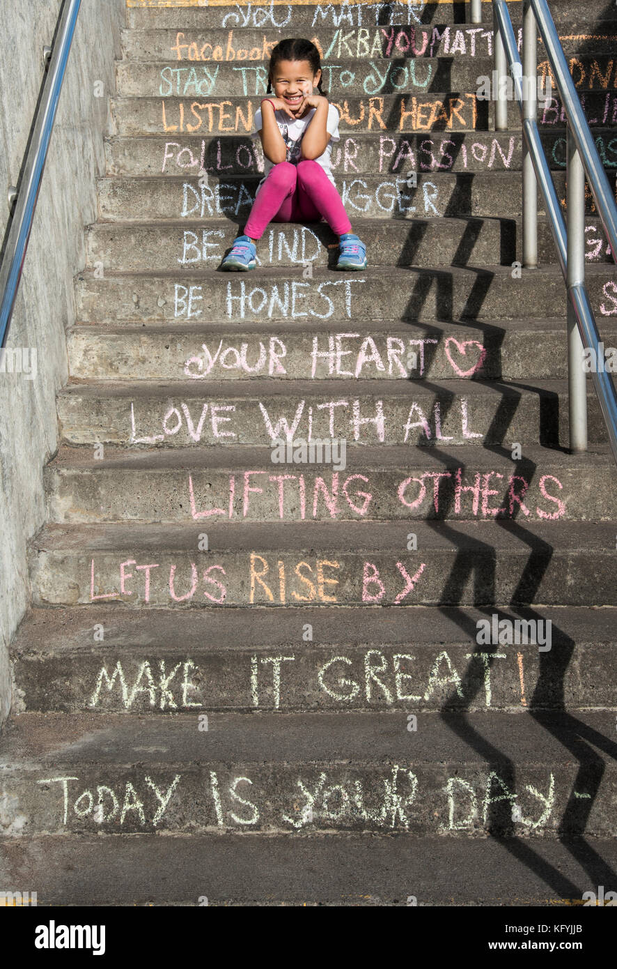 Duluth, Minnesota. Five year old bi-racial girl sitting on the stairs of inspiration. - Stock Image
