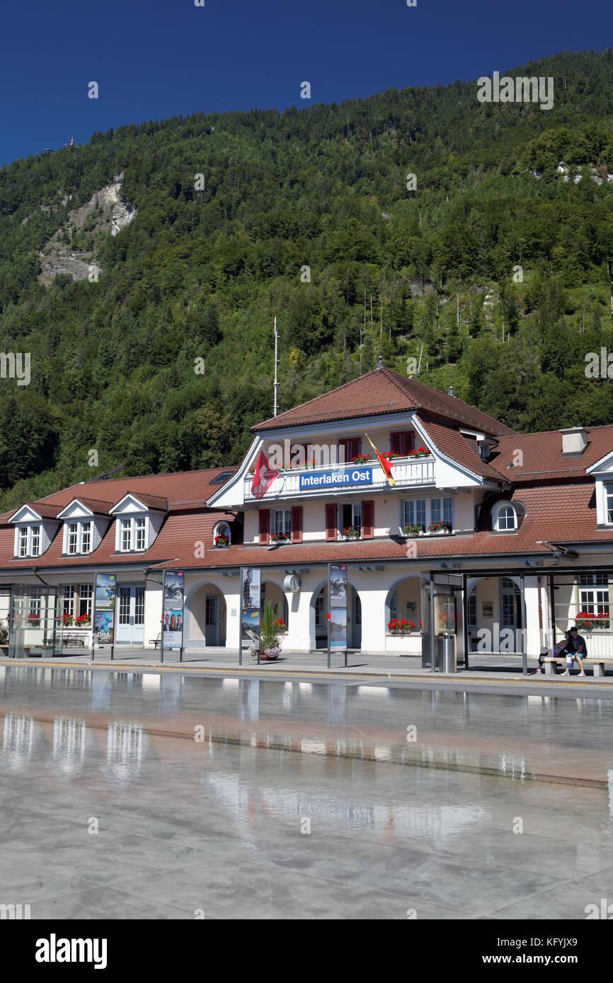 Interlaken Ost or Interlaken East railway station reflected in pool, Interlaken, Switzerland - Stock Image