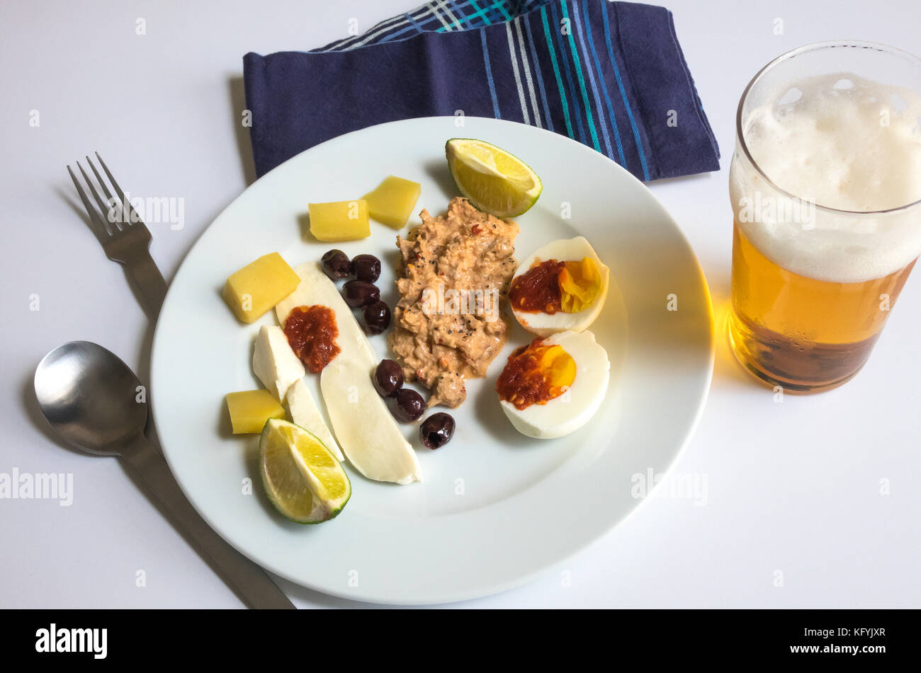 A cold summer lunch, with tuna salad, a spicy hardboiled egg, olives, mozzarella, cheddar, lime and pint ofa larger - Stock Image