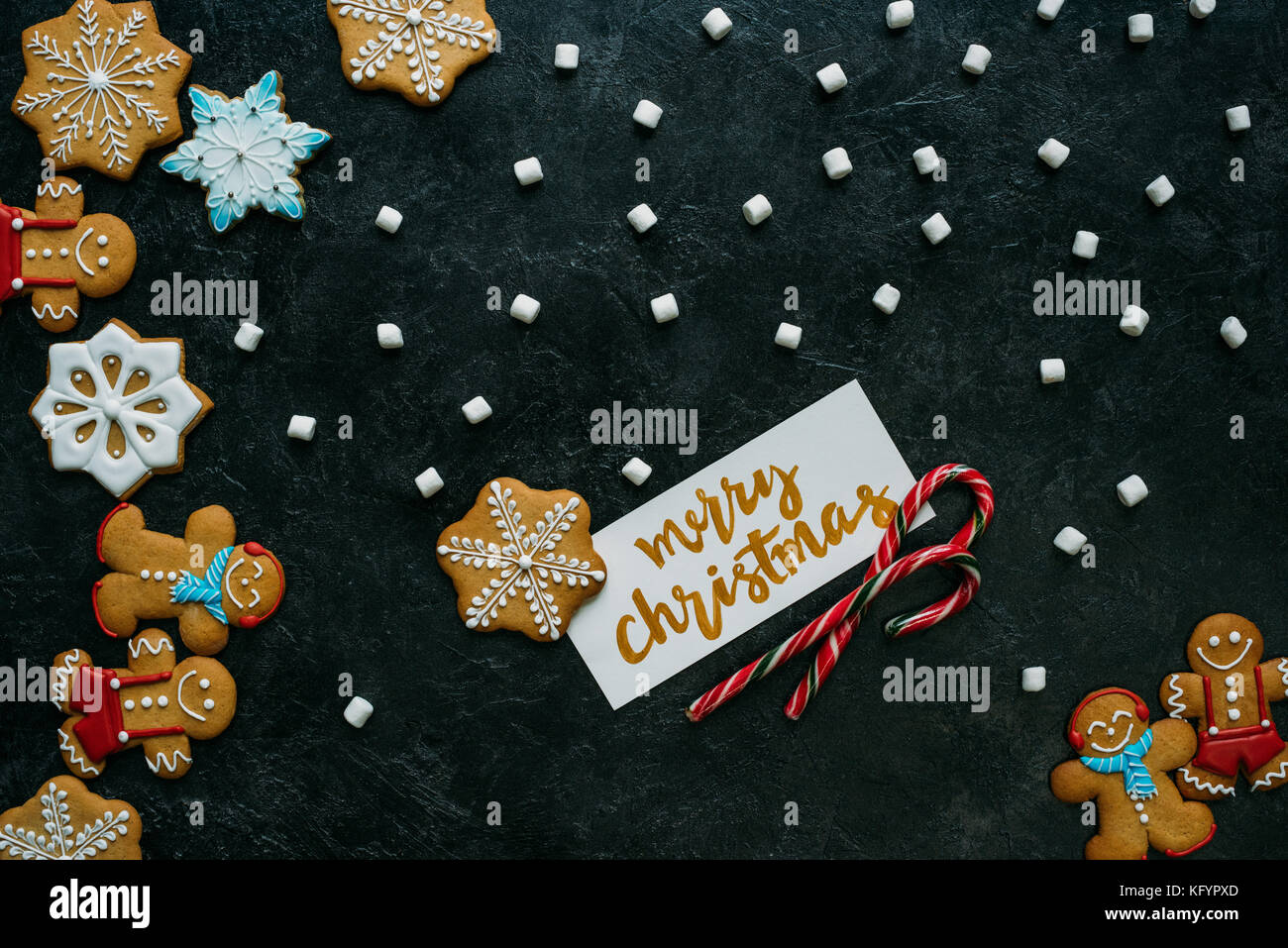 christmas gingerbreads, marshmallows and greeting card - Stock Image